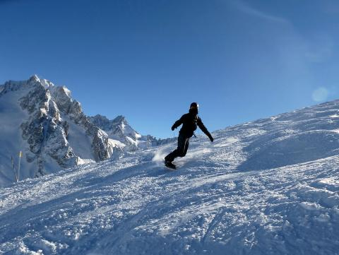 We are going snowboarding on steep slopes, following our ski instructor in Chamonix valley